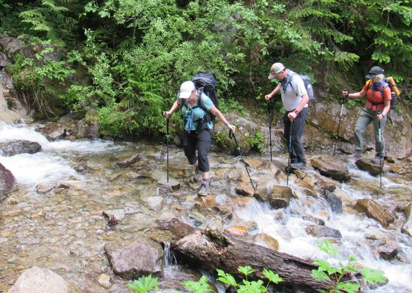 3 hikers cross a stream using hiking poles