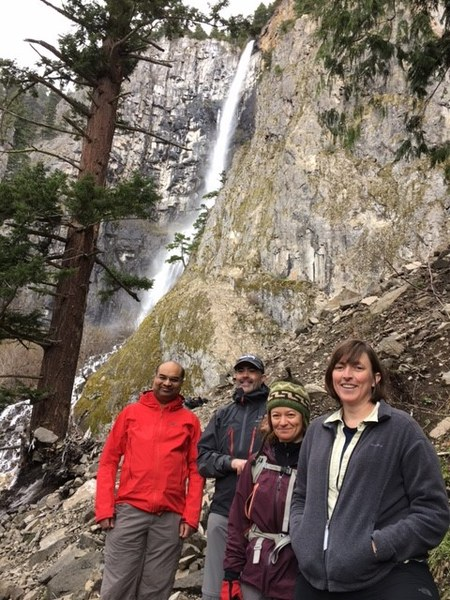 Hikers in front of waterfall