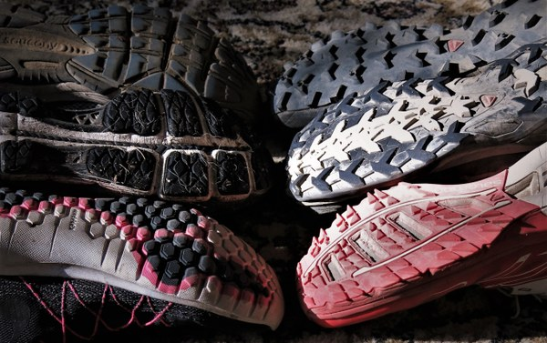 With trail runners on the right and road running shoes on the left, one can easily compare the differences in tread.